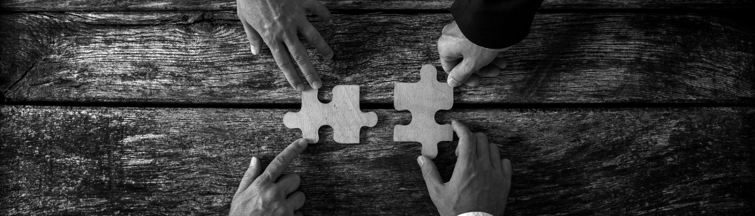 Four successful business men joining two puzzle pieces each being held by two partners rustic wooden background. Conceptual of merger or creative cooperation of two business companies.